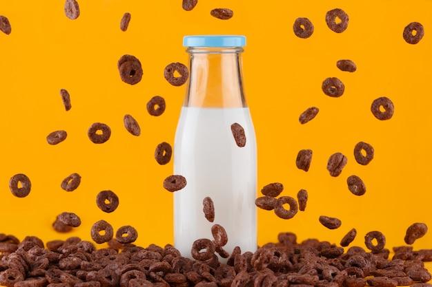 Bottiglia per il latte gialla su giallo. anelli di cereali al cioccolato che cadono.