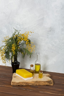 Yellow mimosa flower vase with herbal soap and essential oil bottle on wooden board over table against grey wall