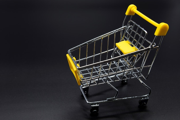 Yellow mini cart or supermarket trolley on black background. online shopping concept by mockup model.