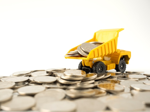 白で隔離されて散らばっているコインの上にコインをロードする黄色のミニチュアトラック