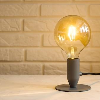 Желтый минималистичный современный светильник в интерьере на фоне кирпичной стены на рабочем столе