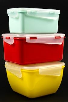 Желтые, мятные и красные пластиковые ланч-боксы на черном фоне. вертикальное фото