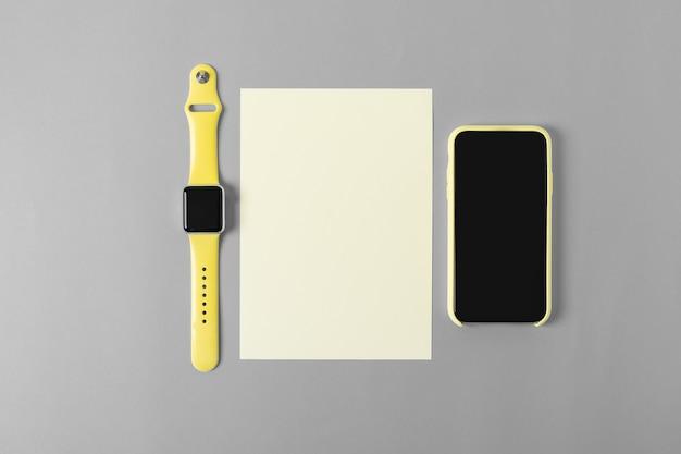 Желтый мобильный телефон и часы на чистом сером офисном столе