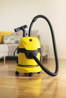 Yellow modern vacuum cleaner in living room. copy space. flat clean vacuuming concept