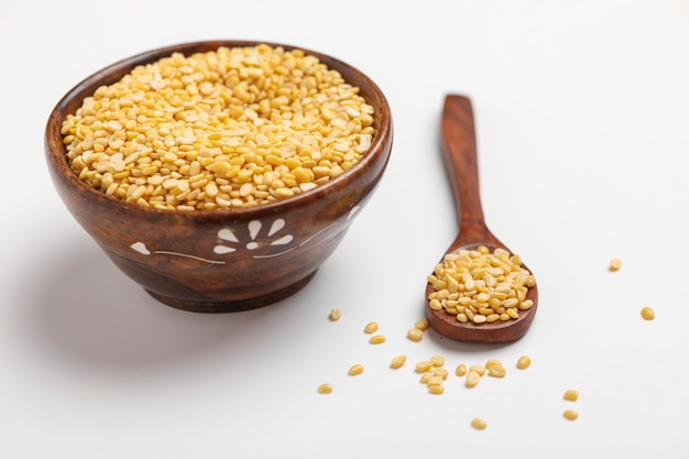 흰색 배경에 나무와 숟가락 그릇에 노란색 moong 녹두 렌즈 콩 펄스 콩