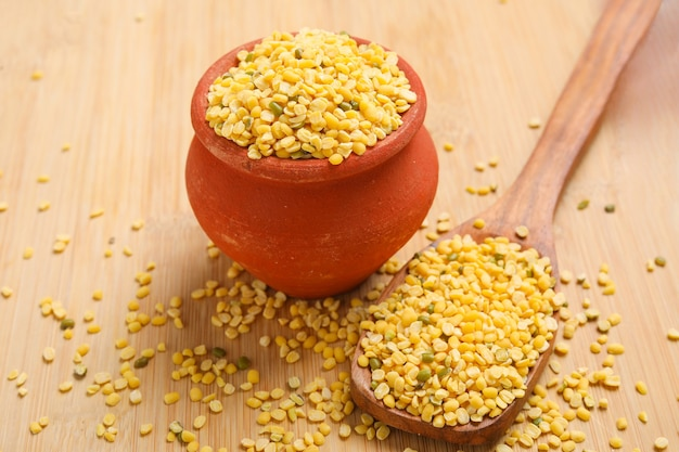 Yellow moong mung dal lentil pulse bean in wooden bowl on wooden background.