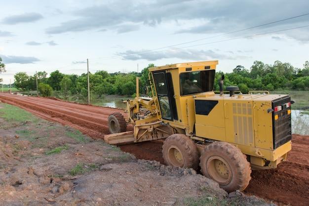 黄色のモーターグレーダー新しい道路の道路建設現場で働く道路。