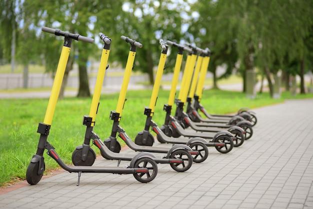 Желтые мотороллеры, расположенные в ряд. система совместного использования скутеров.