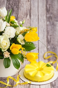Yellow mousse cake and a large spring medley bouquet of beautiful flowers.