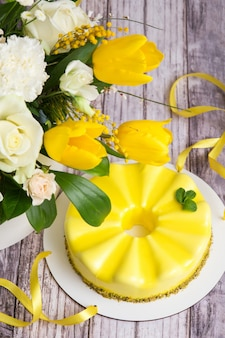 Yellow mousse cake and a large spring medley bouquet of beautiful flowers