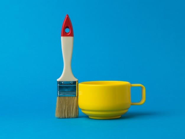 黄色のマグカップと青い背景に長い毛のブラシ。カラートレンド。