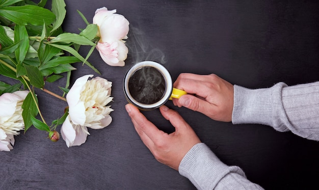 Yellow mug in female hands on black background
