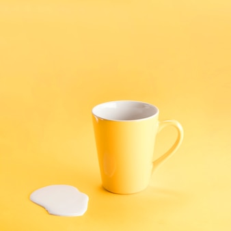Yellow mug with spilled milk