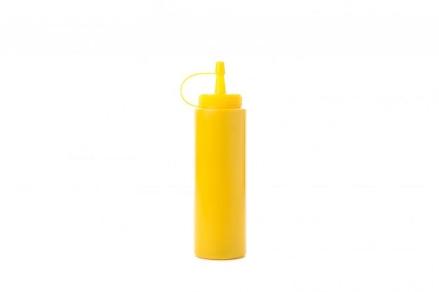 白で隔離される黄色いマスタードボトル