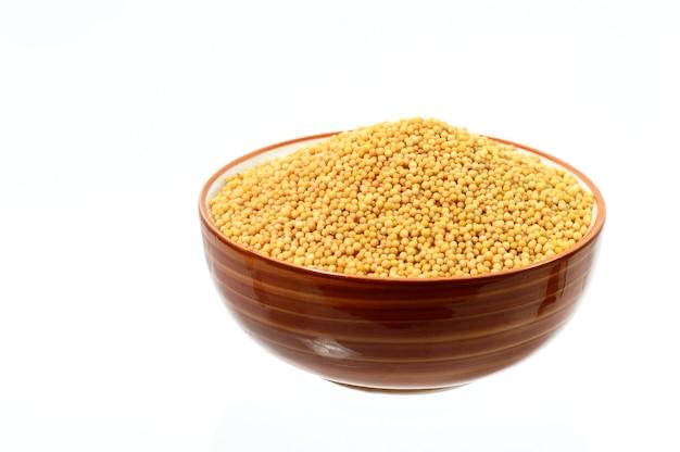 Семена желтой горчицы в миске, изолированные на белом фоне