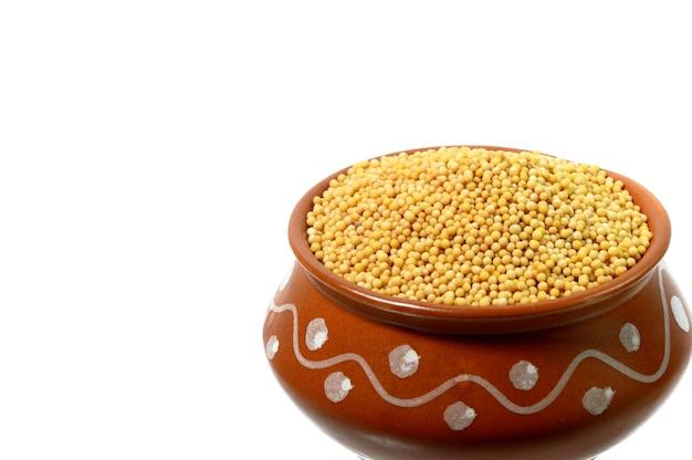 Семена желтой горчицы в глиняном горшке, изолированные на белом фоне
