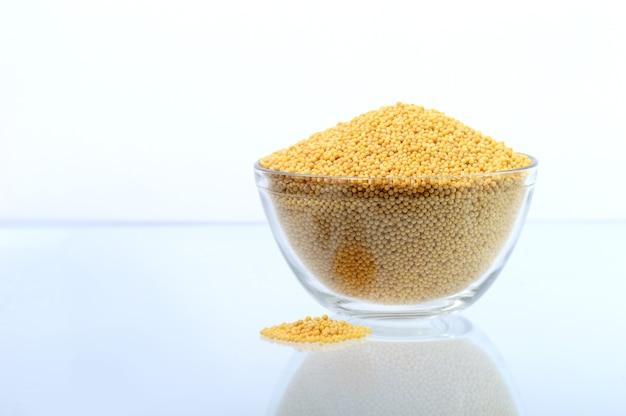 Семена желтой горчицы в стеклянной миске, изолированные на белом фоне