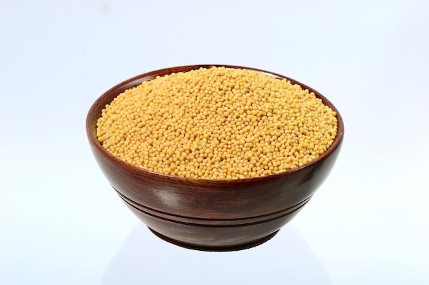 Семена желтой горчицы в деревянной миске, изолированные на белом фоне