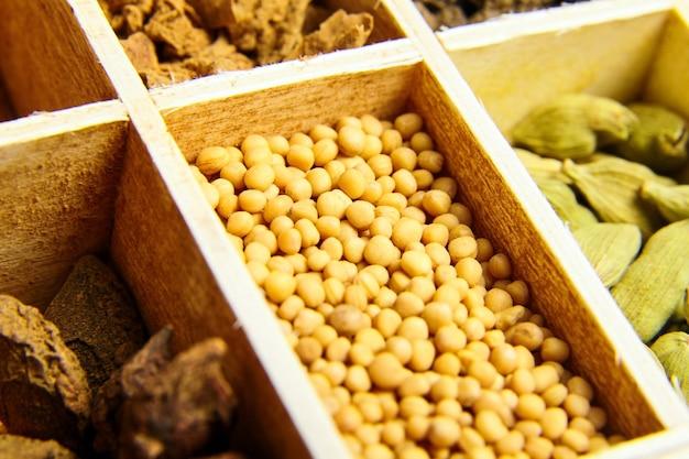 黄色いマスタードシード。木製の箱でさまざまな乾燥スパイス。グリーンカルダモンまたはカルダモンとスターアニスの種子