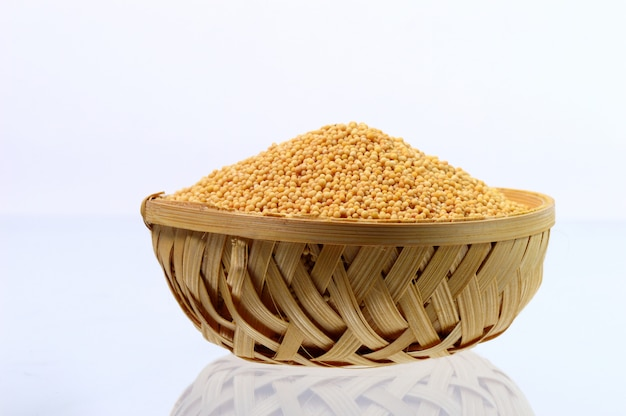 Yellow mustard seeds in wooden basket isolated