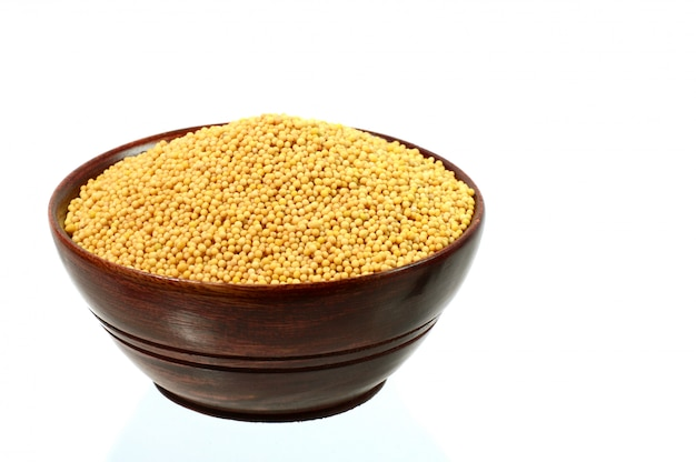 Yellow mustard seeds in wooden bowl isolated