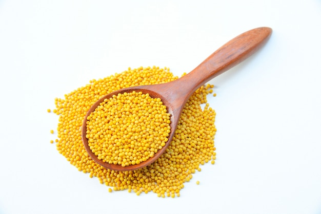 Yellow mustard seeds in the wooden spoon on white background