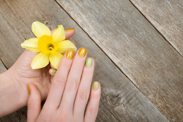 Yellow nail design. female hand with glitter manicure holding narcissus flowers.