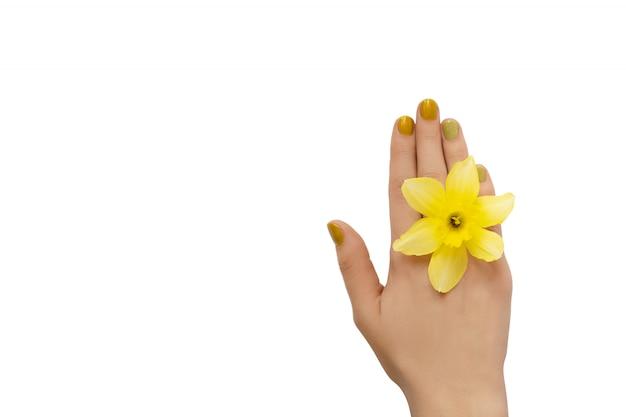 黄色のネイルデザイン。白い背景のキラキラマニキュアで女性の手