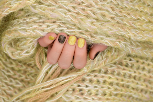 黄色のネイルデザイン。キラキラのマニキュアで手入れの行き届いた女性の手。