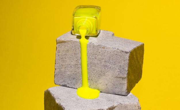 黄色のマニキュアが灰色のコンクリートの石の上を流れます。トレンドカラー