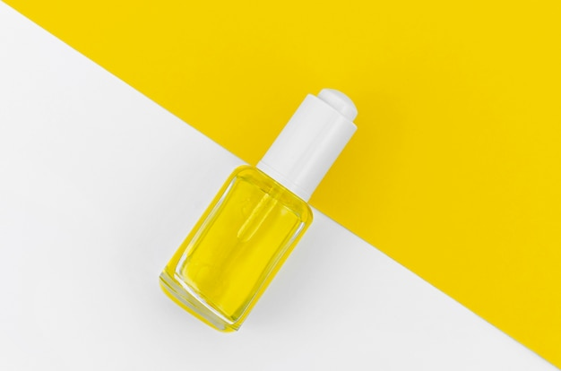 Yellow nail polish on white and yellow background