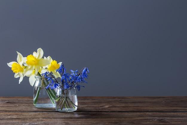 Желтый нарцисс и синие подснежники в вазе на деревянном столе на темной поверхности