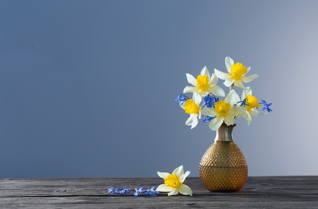 Yellow narcissus and blue snowdrops in vase on wooden table on dark surface