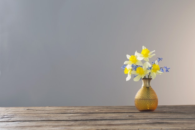 Yellow narcissus and blue snowdrops in vase on wooden table on gray surface