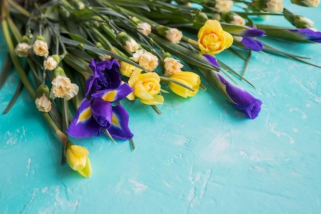 青い背景に分離されたラインフラワーアレンジメントの黄色い水仙の花と紫色の菖蒲。美しい春の花幸せな母の日。コピースペース