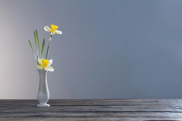 어두운 배경에 나무 테이블에 꽃병에 노란색 수선화