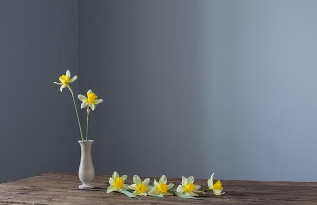 Желтый нарцисс в вазе на деревянном столе на темной поверхности