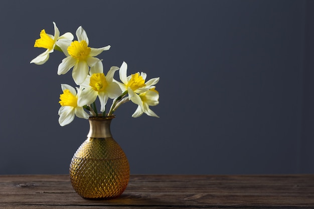 Yellow narcissus in vase on wooden table on dark surface