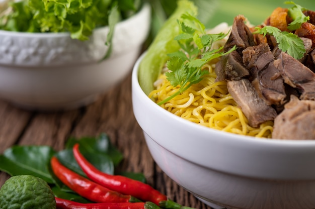 Yellow noodles in a cup with crispy pork, slices of pork, and meatballs together with thai food-style noodles