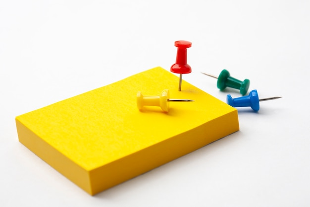 Yellow note paper and pushpin