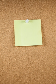 Yellow note papers on cork board background.