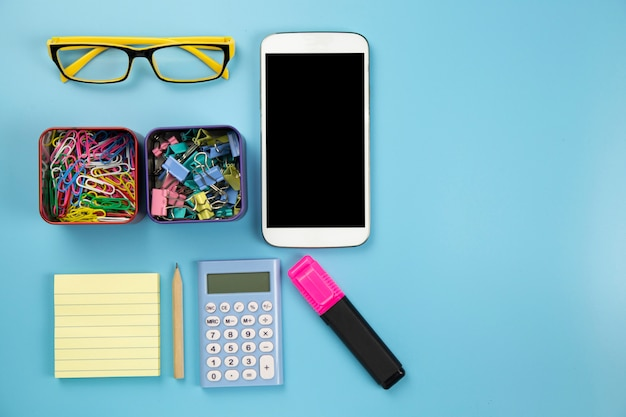 Yellow notebook mobile phone calculator and hilight marker glasses clip on blue background pastel style with copyspace flatlay clipping path on screen moblie