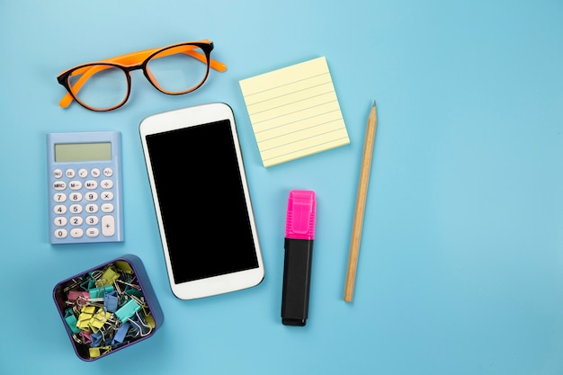 Yellow notebook mobile phone calculator and hilight marker orange glasses on blue background pastel style with copyspace flatlay clipping path on screen moblie
