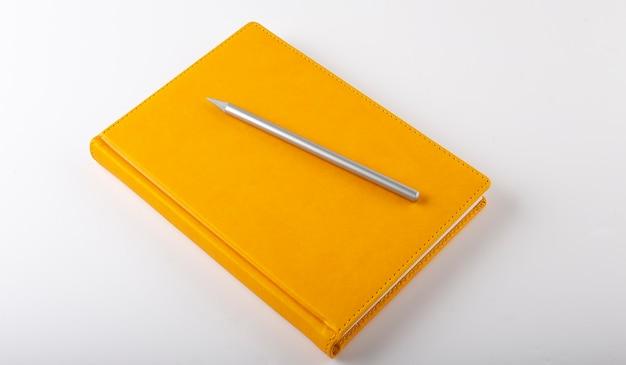 Желтый блокнот на белом фоне с ручкой
