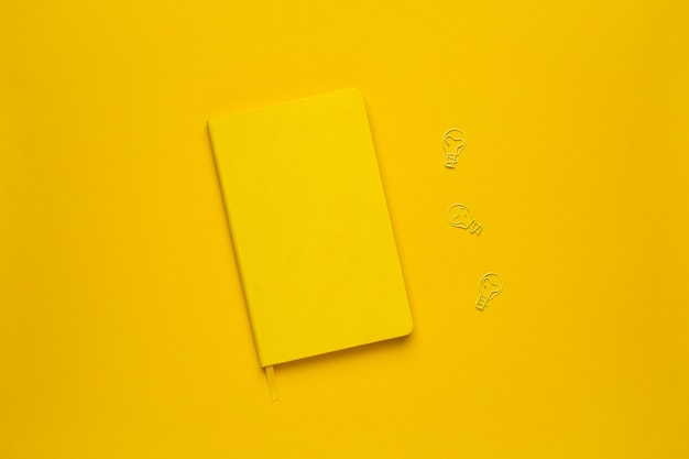 Yellow notebook and paperclip light bulb idea on yellow