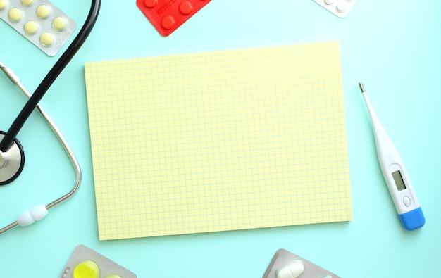 청진기 옆에 있는 노란색 노트북, 파란색 배경에 약. 의료 개념