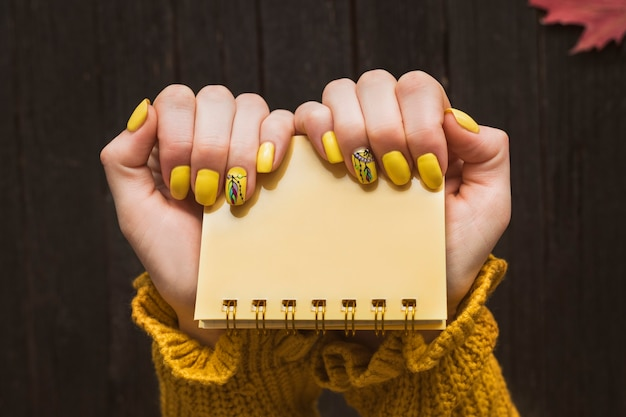 Yellow notepad in female hands. manicure with a pattern.