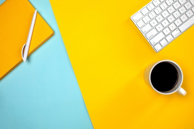 Yellow notepad keyboard and cup of coffee