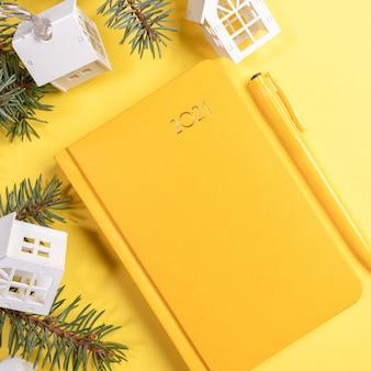 Желтый блокнот или ежедневник на 2021 год с еловыми ветками и декором. вид сверху.