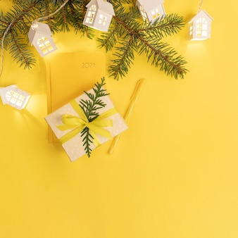 Желтый блокнот или ежедневник на 2021 год с еловыми ветками и подарочной коробкой. вид сверху.